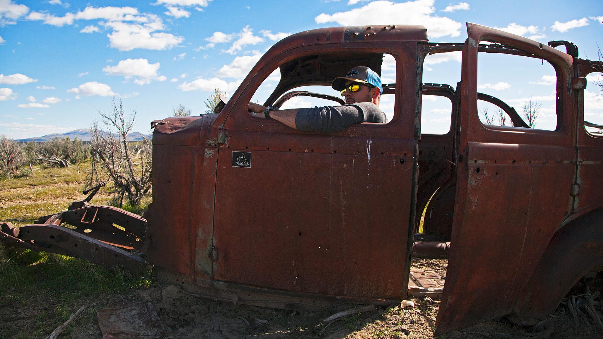 Man sitting in rusty car
