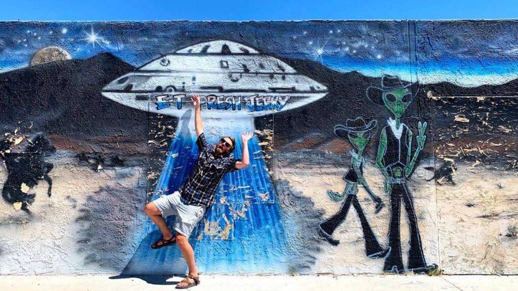 Man posing in front of alien mural