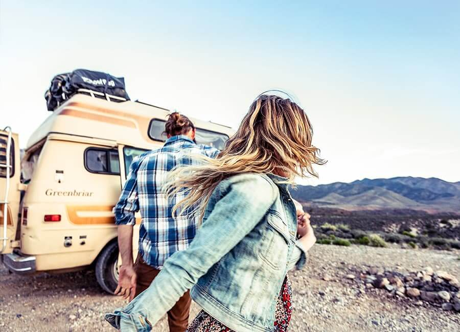 Two people near a van in front of mountains